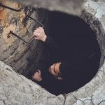 Man climbing out of a hole in the ground