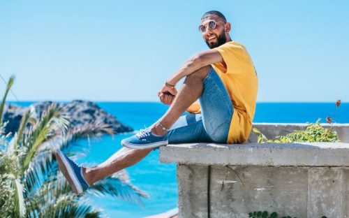 Man happy about his credit score sitting outside near the ocean on a sunny day
