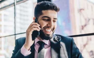 Man wearing suit using his cell phone while smiling