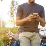 Man using his cell phone outside while sitting on his blue bike