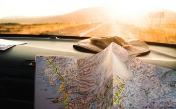 Real map sitting on dash of car driving down the road towards a sunset