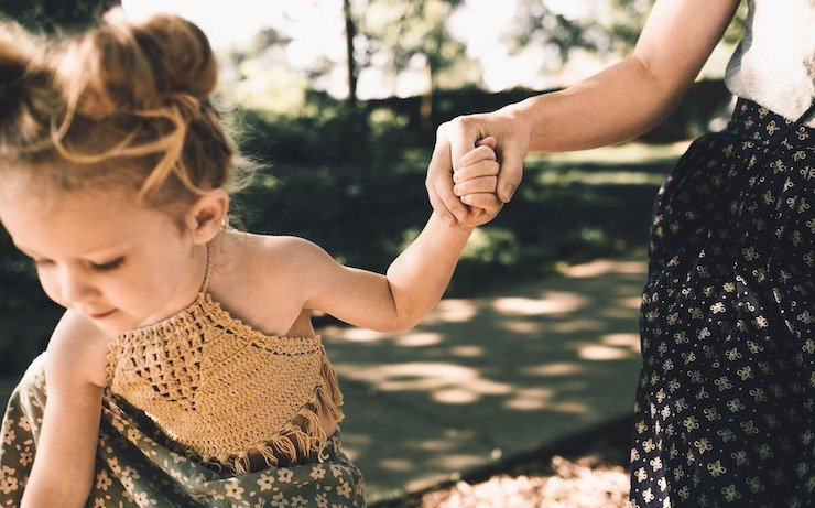 Mom and daughter playing outside while holding hands