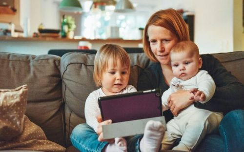Mom holding her two children while looking at their tablet while sitting on their couch