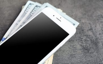 Old smartphone sitting on a pile of cash