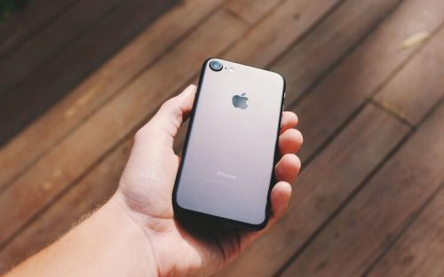 Man holding an iphone in the sun with wood floor in the background