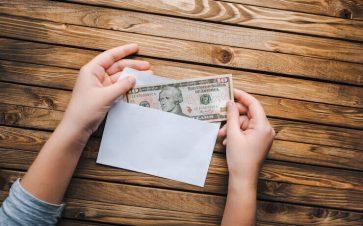 Woman putting 10 dollar bin into an envelope budgeting