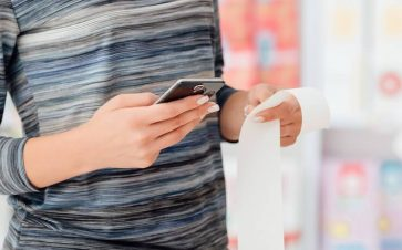 Woman wearing black and blue striped shirt holding a receipt and cell phone