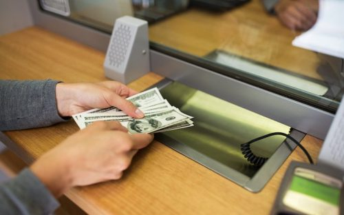 Woman withdrawing hundreds of dollars from bank teller at a bank