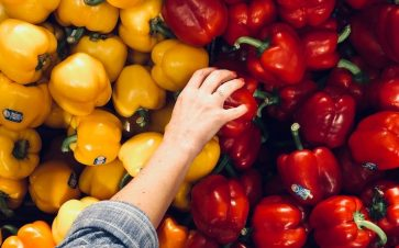 Personal grocer picking out red bell pepper near yellow bell peppers