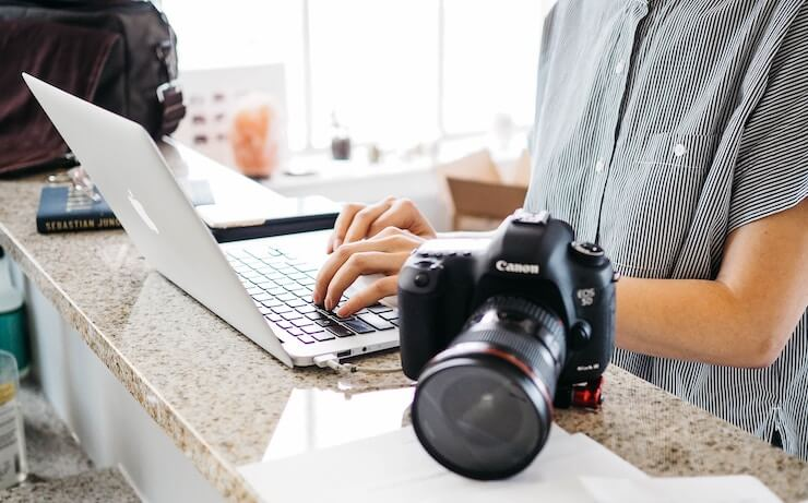 Photographer uploading images to their computer to sell online and make money