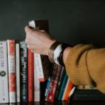 Woman picking a book out of shelf full used books while wearing brown sweater and bangles