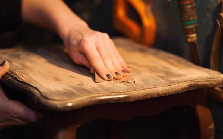 Person wearing black nail polish sanding a chair to refinish the wood surface