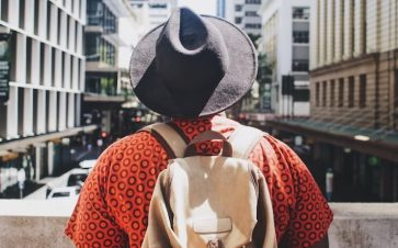 Young man wearing a black hat a back pack and an orange shirt looking out at the city view