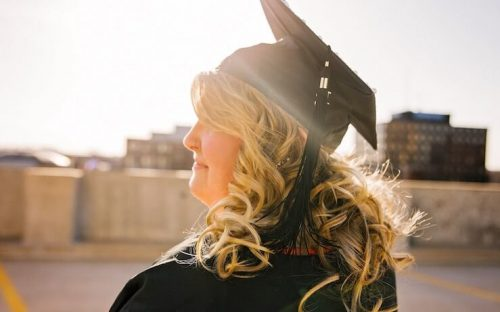 Graduate looking to the horizon while smiling with big blonde curls
