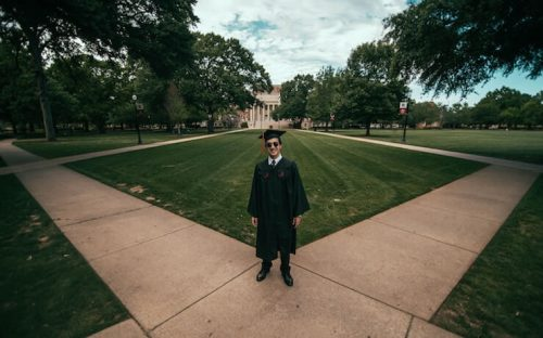 Student standing on campus happy that he graduated
