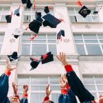 Students throwing their graduation caps in front of their school