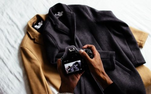 Person taking photo of two jackets that are for sale