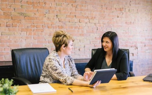 Two women looking into gusto payroll