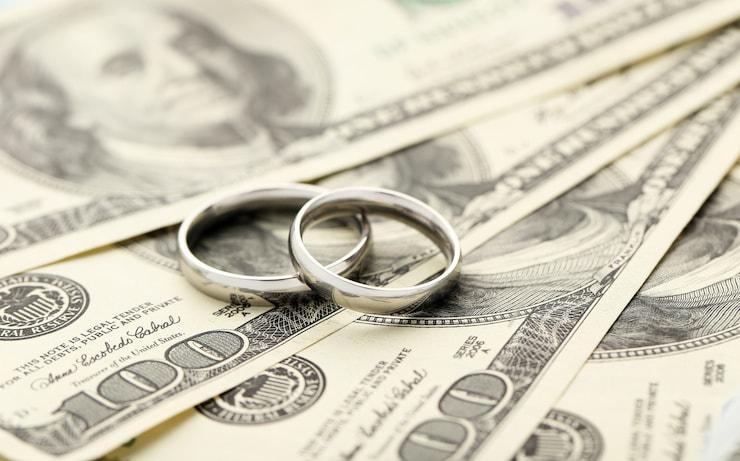 Wedding rings sitting on 100 dollar bills