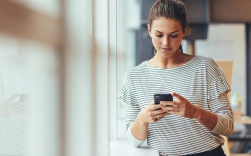Woman wearing striped shirt looking at her cell phone at truebill app