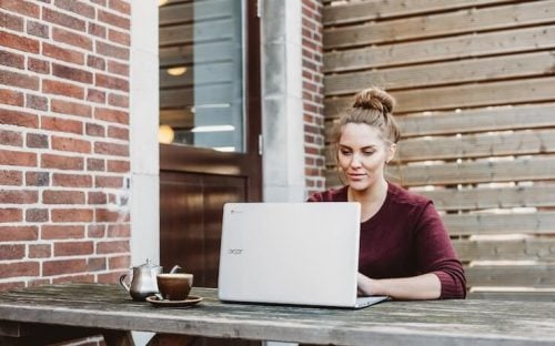 Woman with a messy bun working on an acer laptop outside on picnic table next to a brick wall