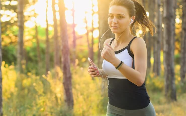 Woman running outside while using an app to track progress