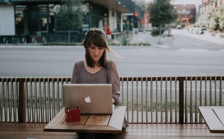 Woman using an apple computer outside at a cafe