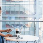 Curly haired woman next to wall of windows using her laptop holding her cell phone with travel coffee cup