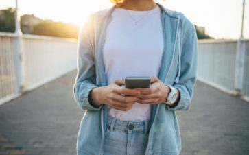 Woman wearing her cell phone outside during sunset