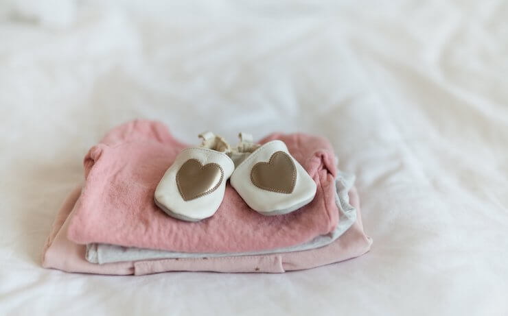 Baby shoes with gold heart on them sitting on top of pink clothing folded on a bed