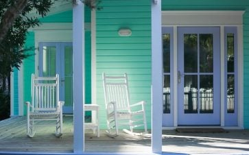 Blue green beach house with a large porch with white classic rocking chairs
