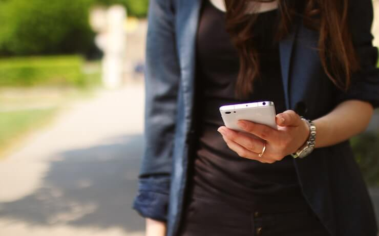 Business woman wearing a blue jacket while wearing a black tank top holding her cell phone while walking outside