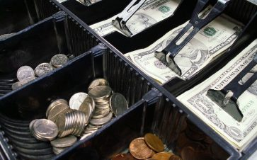Cash and coins in a register drawer of a cash register