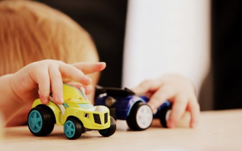 Young child playing with toy cars on a wood table
