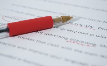 Close up photo of proofreading on paper with a red pen