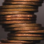 Close up photo of pennies stacked up with blurry background