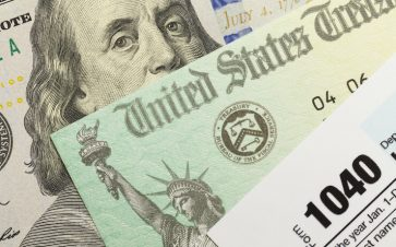 Close up photo of tax form, tax return and hundred dollar bill