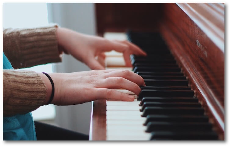 student's hands playing the piano