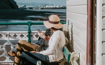 A woman wearing a large hat sitting next to her friend at bench enjoying the water nearby