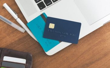 Blue credit cards sitting on a silver laptop next to pens and a wallet with more cards inside
