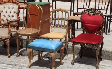 Old different pieces of furniture and chairs sitting on sidewalk