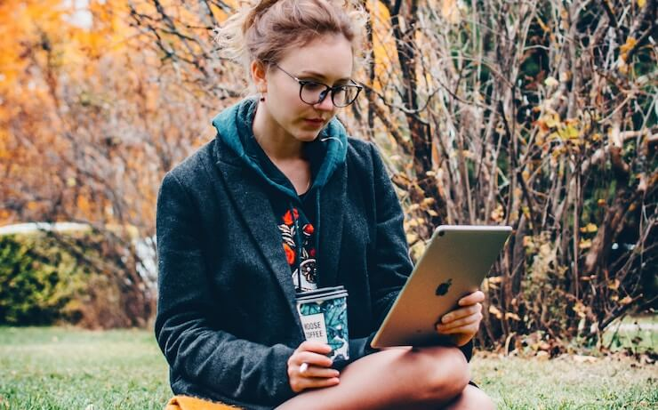 girl researching aspiration bank on ipad outside while drinking coffee