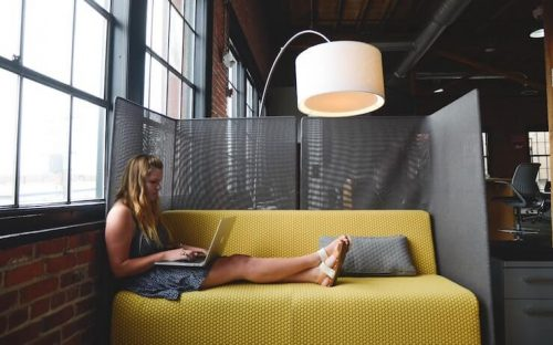 Blond girl using her computer on a yellow couch