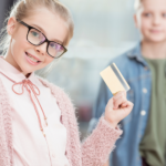 two kids holding up a greenlight debit card