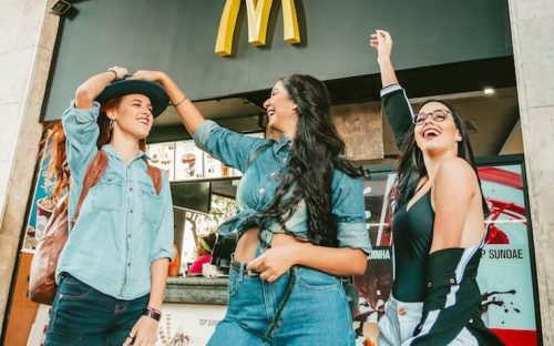 Group of teen girls laughing in front of a mcdonalds