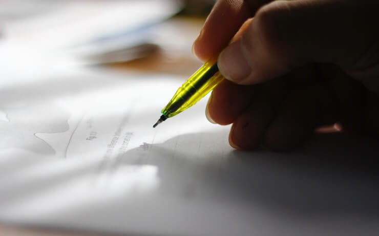 person holding a yellow pencil to write or sign a document