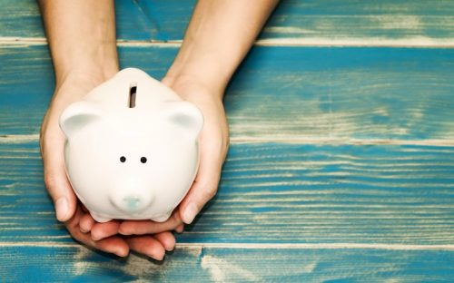 Persons hands holding white piggy bank on blue tinted wood table