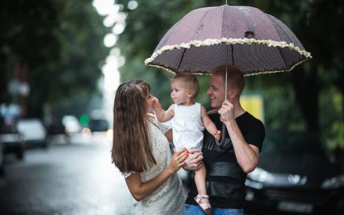 A happy family outside holding umbrella to protect from rain and sun