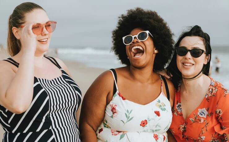 3 happy girls laughing while at the beach talking about future retirement