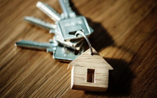 Keys for house laying on a wood table with house keychain